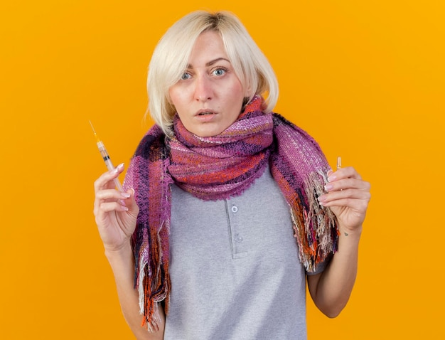 Zszokowana młoda blondynka chora słowiańska chusta na sobie szalik trzyma strzykawkę