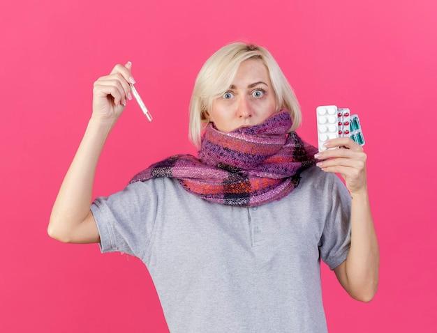 Zszokowana młoda blondynka chora słowiańska kobieta nosi szalik trzyma paczki pigułek medycznych