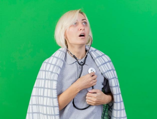 Zszokowana młoda blondynka chora słowiańska kobieta owinięta w kratę trzyma stetoskop patrząc w górę na białym tle na zielonej ścianie z miejsca na kopię