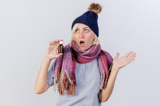 Zszokowana młoda blondynka chora słowiańska kobieta w czapce zimowej i szaliku stoi z podniesioną ręką i trzyma lekarstwo w szklanej butelce odizolowanej na białej ścianie z miejscem na kopię