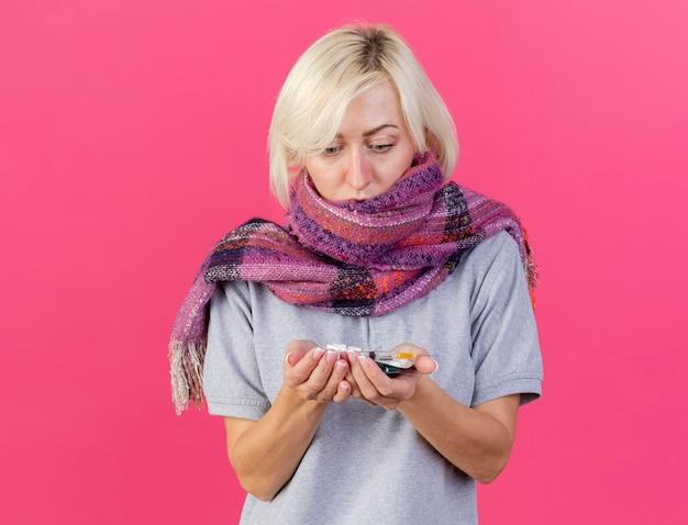 Zszokowana młoda blondynka chora słowiańska kobieta w szaliku trzyma i patrzy na opakowania tabletek medycznych