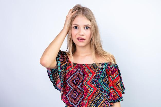 Zszokowana młoda blondynka słowiańska kładzie rękę na głowie i