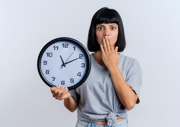 Zszokowana młoda brunetka dziewczynka kaukaski kładzie rękę na usta trzymając zegar