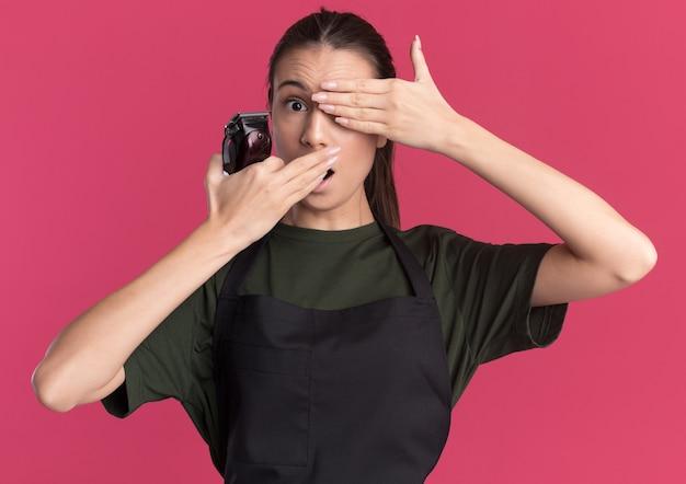 Zszokowana młoda brunetka fryzjerka w mundurze cobers oko i usta trzymająca maszynkę do strzyżenia