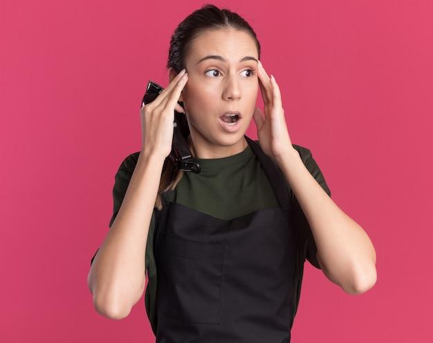 Zszokowana młoda brunetka fryzjerka w mundurze kładzie ręce na skroniach, trzymając maszynkę do strzyżenia włosów odizolowaną na różowej ścianie z miejscem na kopię
