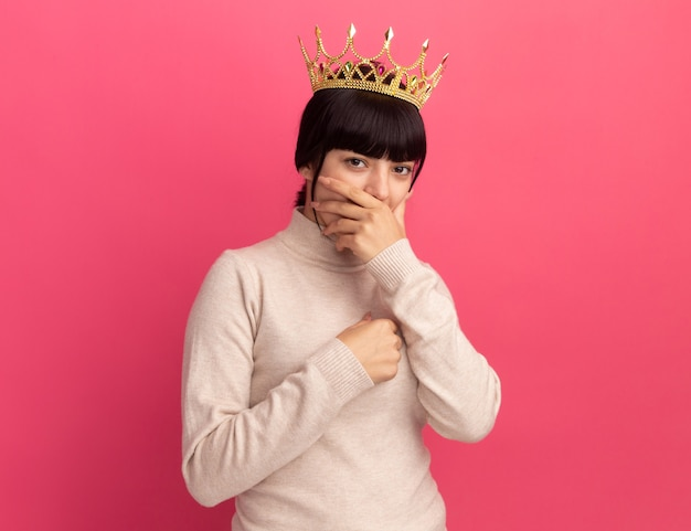 Zszokowana młoda brunetka kaukaska dziewczyna z koroną kładzie rękę na ustach i trzyma na klatce piersiowej odizolowaną na różowej ścianie z miejscem na kopię