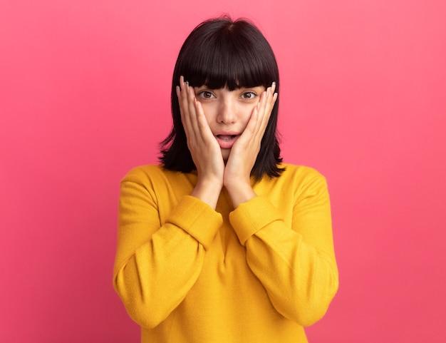 Zszokowana młoda brunetka kaukaski dziewczyna kładzie ręce na twarzy i patrzy na aparat na różowo