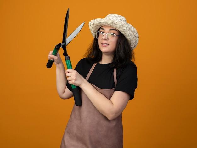 Zszokowana młoda brunetka ogrodnik kobieta w okularach optycznych iw mundurze na sobie kapelusz ogrodniczy trzyma nożyce ogrodowe na białym tle na pomarańczowej ścianie