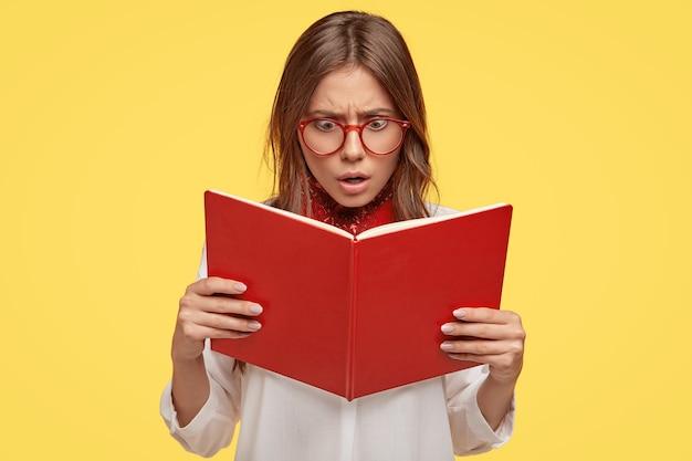 Zszokowana młoda brunetka w okularach pozuje na żółtej ścianie