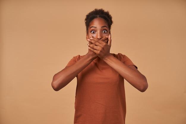 Zszokowana młoda ciemnoskóra brunetka zakrywa usta uniesionymi dłońmi i ze zdumieniem zaokrągla swoje brązowe oczy, stojąc na beżu