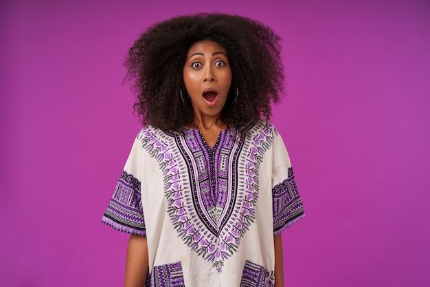 Zszokowana młoda ciemnoskóra kobieta o swobodnej fryzurze, stojąca na fioletowo z opuszczonymi rękami, z szeroko otwartymi ustami i zaokrąglonymi oczami