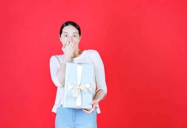 Zszokowana młoda dama trzymająca owinięte pudełko na prezent