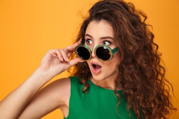 Zszokowana młoda dama w okularach przeciwsłonecznych.