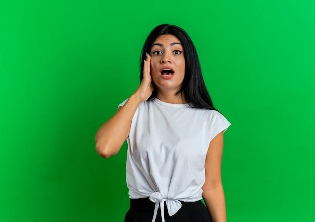 Zszokowana młoda dziewczyna kaukaski kładzie rękę na twarzy patrząc