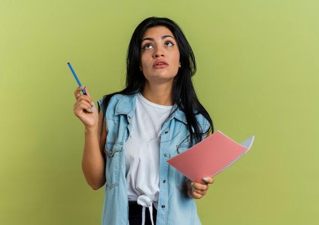 Zszokowana młoda dziewczyna kaukaski trzyma pióro i notatnik patrząc na białym tle na oliwkowym tle z miejsca na kopię