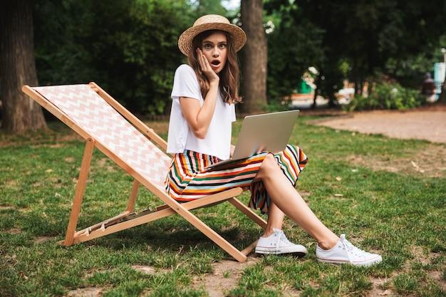 Zszokowana młoda dziewczyna siedzi z laptopem w parku na świeżym powietrzu