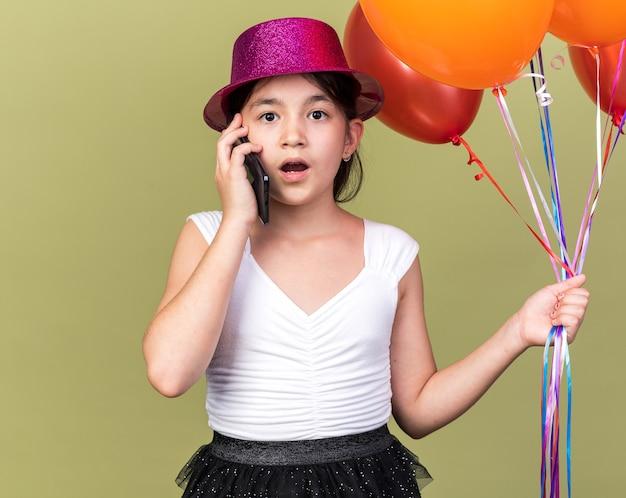 Zszokowana młoda dziewczynka kaukaski z fioletowym kapeluszem strony, trzymając balony z helem, rozmawiając przez telefon na białym tle na oliwkowej ścianie z miejsca na kopię