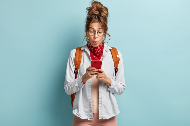 Zszokowana młoda hipsterka niespodziewanie patrzy na telefon komórkowy, odbiera nieoczekiwaną wiadomość, niesie plecak