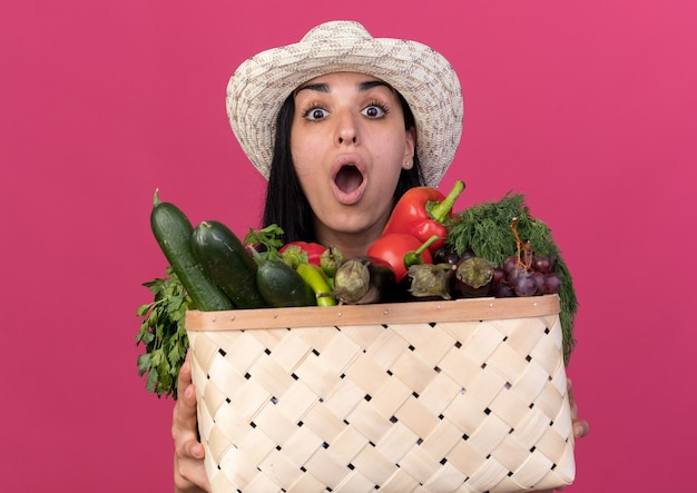 Zszokowana młoda kaukaska dziewczyna ogrodniczka ubrana w mundur i kapelusz, trzymająca kosz warzyw na białym tle na różowej ścianie