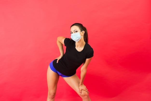 Zszokowana młoda kobieta fitness w masce sterylnej odzieży sportowej pracy na białym tle na żółtym tle portret studio.