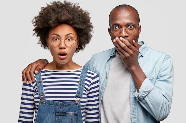 Zszokowana młoda kobieta i mężczyzna otwierają szeroko usta w oszołomieniu, obejmują się