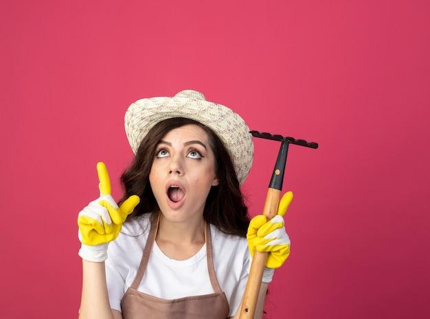 Zszokowana młoda kobieta ogrodnik w mundurze na sobie kapelusz ogrodniczy i rękawiczki trzyma prowizję patrząc i skierowaną w górę na białym tle na różowej ścianie