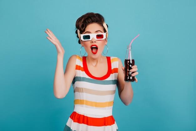 Zszokowana młoda kobieta pozuje w okularach 3d. pinup girl w pasiastej sukience trzymając butelkę sody na niebieskim tle.