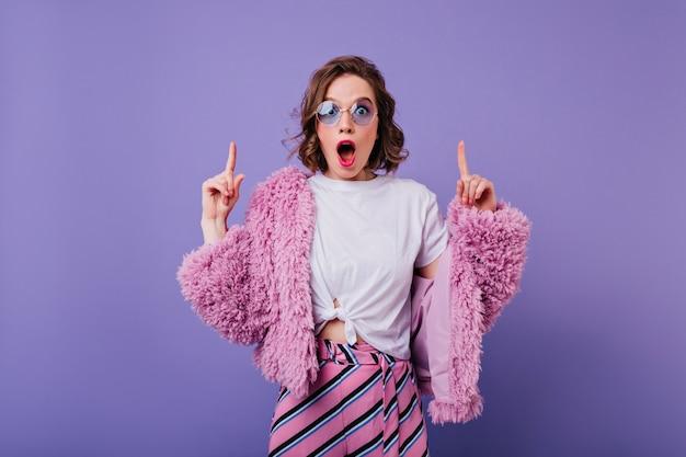 Zszokowana młoda kobieta pozuje w różowym futrze z falowaną fryzurą. piękna kaukaski zaskoczona dziewczyna w okularach przeciwsłonecznych na białym tle na fioletowej ścianie.