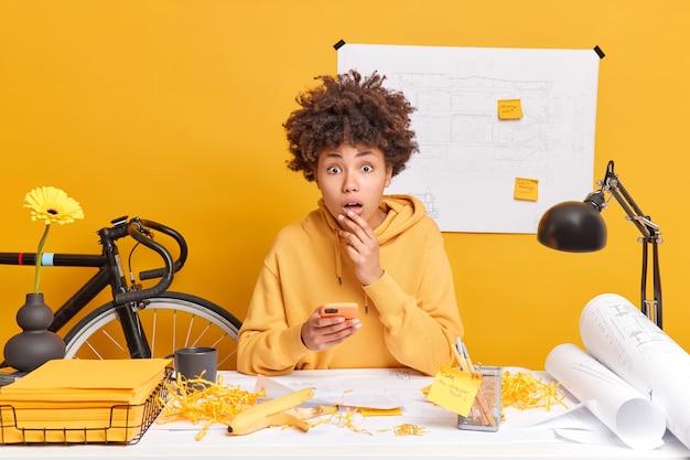 Zszokowana młoda kobieta rasy mieszanej, zajęta, patrzy zdziwiona, używa smartfona, pozuje w przestrzeni coworkingowej, ma produktywną pracę przy biurku w otoczeniu szkiców i planów