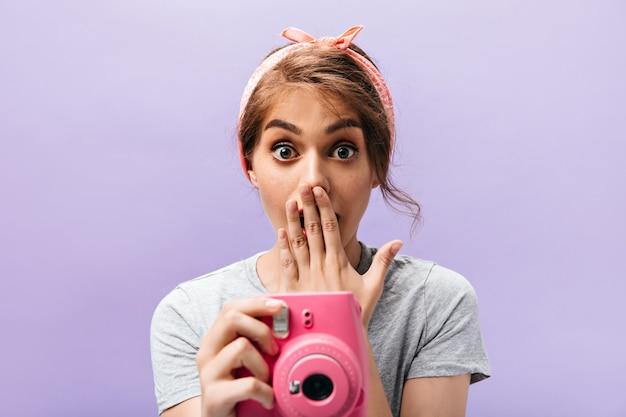 Zszokowana młoda kobieta trzyma różowy aparat. fajna dziewczyna z letnią stylową opaską i stylową fryzurą na na białym tle.