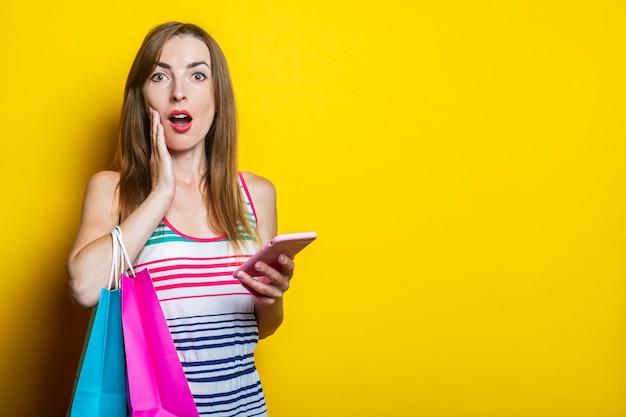 Zszokowana młoda kobieta trzymająca dłonie na policzku, z telefonem i torbami zakupów