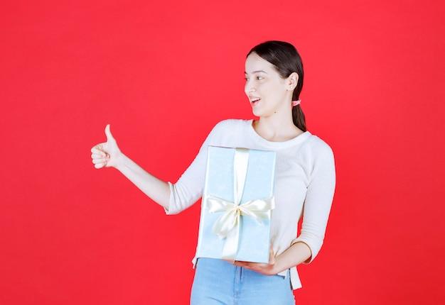 Zszokowana młoda kobieta trzymająca pudełko i wskazująca kciukiem w górę
