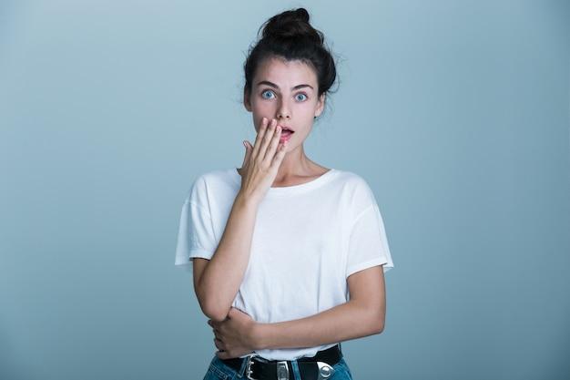 Zszokowana młoda kobieta ubrana w t-shirt na białym tle na niebieskim tle