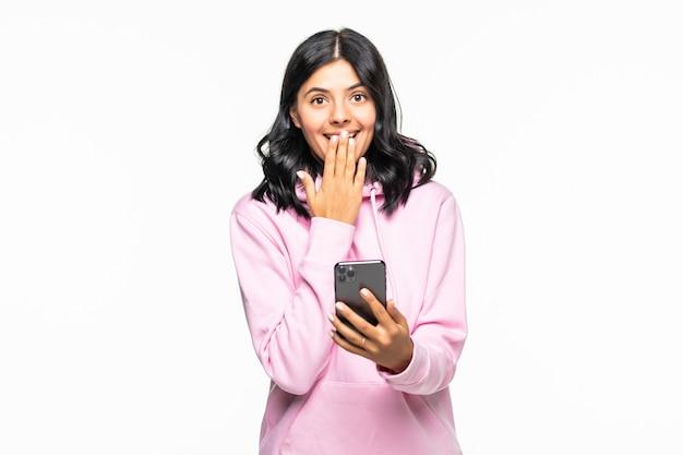 Zszokowana młoda kobieta używając telefonu komórkowego, wpisując wiadomość sms w luźnej bluzie z kapturem pozuje na białym tle na szarej ścianie