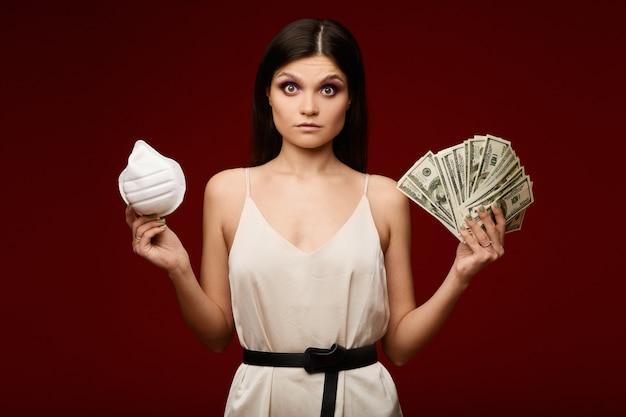 Zszokowana młoda kobieta w lekkiej sukience trzyma maskę respiratora w jednej ręce i paczkę pieniędzy w drugiej. pojęcie kryzysu pandemicznego, epidemicznego i finansowego