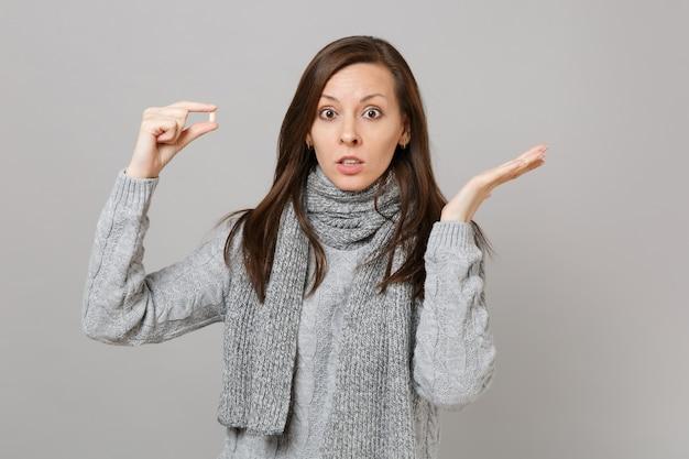 Zszokowana młoda kobieta w szarym swetrze, szalik rozkładający się za ręce trzymając tabletkę z lekiem, pigułkę aspiryny na białym tle na tle szarej ściany. zdrowy styl życia, leczenie chorych chorych, koncepcja zimnej pory roku.