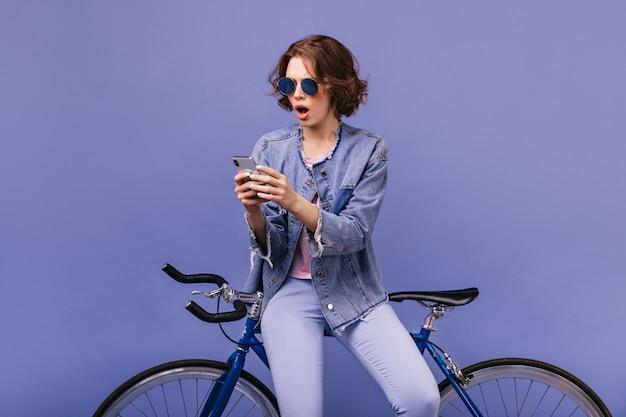 Zszokowana młoda kobieta z brązowymi włosami, patrząc na ekran telefonu. spektakularna modelka siedząca na rowerze i korzystająca z komórki.