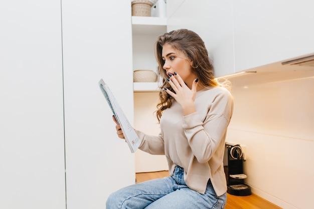 Zszokowana młoda kobieta z czarnymi paznokciami czyta wiadomości w domu