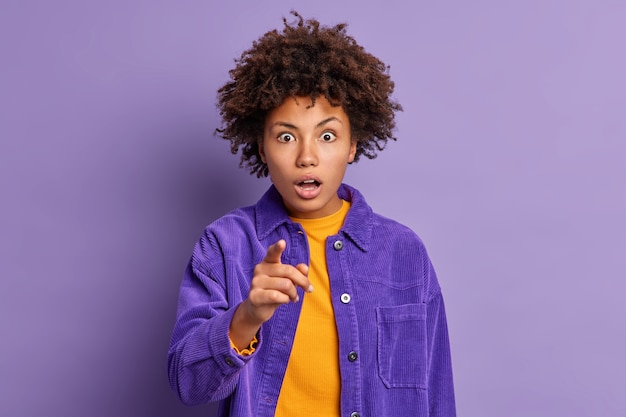 Zszokowana młoda kobieta z kręconymi włosami wpatruje się w oszołomiony wyraz twarzy wskazując palcem wskazującym wprost na ciebie, wstrzymując oddech od zachwytu ubrana w modny strój.