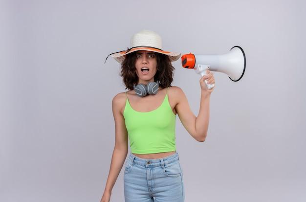 Zszokowana młoda kobieta z krótkimi włosami w zielonej bluzce w słuchawkach w kapeluszu przeciwsłonecznym, zaskakująca i trzymająca megafon na białym tle