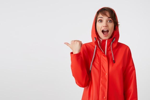 Zszokowana młoda, krótkowłosa dama w czerwonym płaszczu przeciwdeszczowym, z szeroko otwartymi ustami, chce zwrócić twoją uwagę, wskazuje palcem na miejsce na kopię. na stojąco. łał! niewiarygodne wieści!