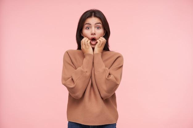 Zszokowana młoda ładna brązowowłosa kobieta z naturalnym makijażem trzymająca twarz z podniesionymi rękami, patrząc z przodu z szeroko otwartymi oczami i ustami, odizolowana na różowej ścianie