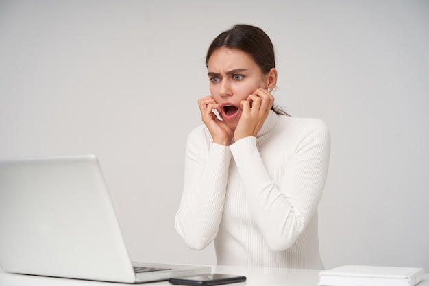 Zszokowana młoda ładna brunetka kobieta z naturalnym makijażem, trzymając podniesione ręce na twarzy, patrząc przestraszony na ekran swojego laptopa, odizolowany na białej ścianie