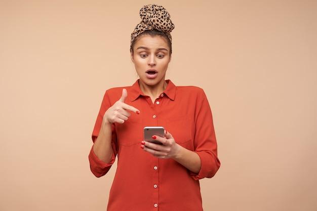 Zszokowana młoda ładna brunetka kobieta z opaską, oszołomiona patrząc na swój telefon i pokazująca palcem wskazującym na ekranie, odizolowana na beżowej ścianie
