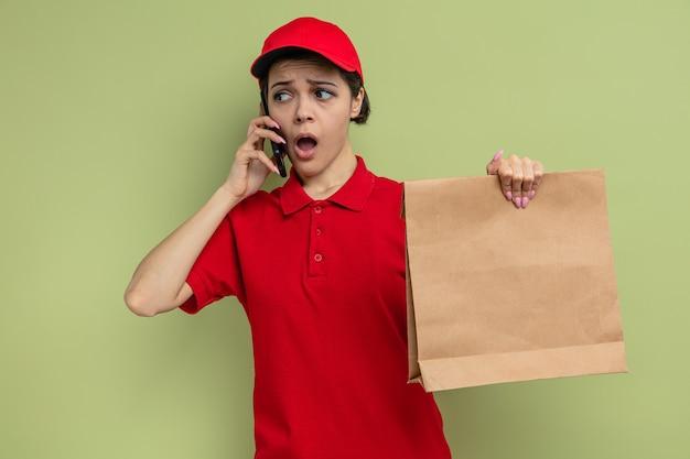 Zszokowana młoda ładna dostawa kobieta rozmawia przez telefon i trzyma papierowe opakowanie na żywność