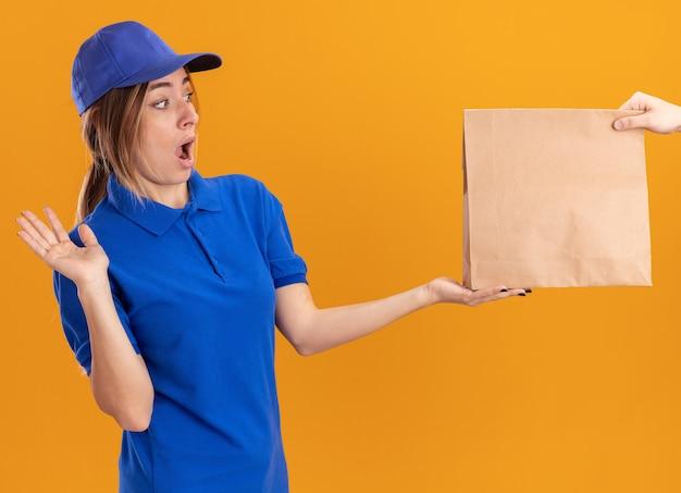 Zszokowana młoda ładna dziewczyna w mundurze dostawy bierze papierową paczkę od kogoś na pomarańczowo