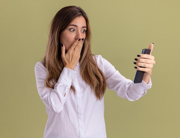 Zszokowana młoda ładna kaukaska dziewczyna kładzie rękę na ustach, trzymając i patrząc na telefon