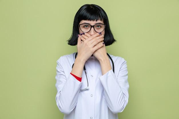 Zszokowana młoda ładna kaukaska kobieta w okularach w mundurze lekarza ze stetoskopem zakrywającym usta rękami