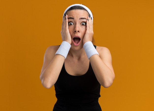 Zszokowana młoda, ładna wysportowana dziewczyna nosząca opaskę i opaski trzymające ręce na twarzy