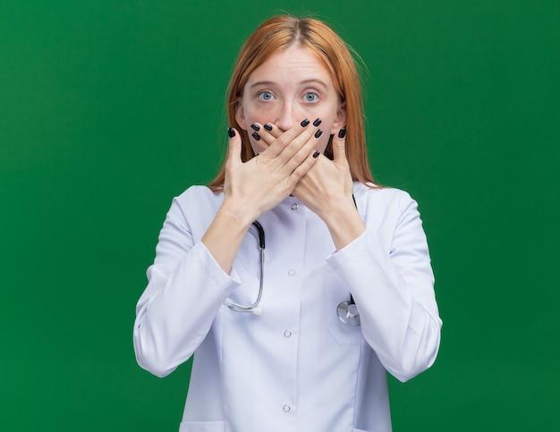 Zszokowana młoda lekarka imbiru ubrana w szatę medyczną i stetoskop zakrywający usta obiema rękami na zielonej ścianie